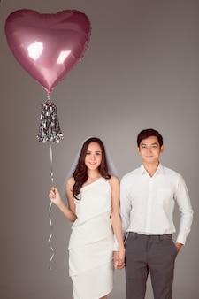 Junges attraktives asiatisches paar, mann, der weißes hemd trägt, frau, die weißes kleid mit hochzeitsschleier trägt, der zusammen händchen haltend steht. frau mit ballon. konzept für die fotografie vor der hochzeit.