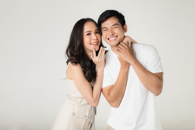 Junges attraktives asiatisches paar, mann, der weißes t-shirt und beige hosen trägt, frau, die beige kleid trägt. sich gegenseitig necken. konzept für die fotografie vor der hochzeit.