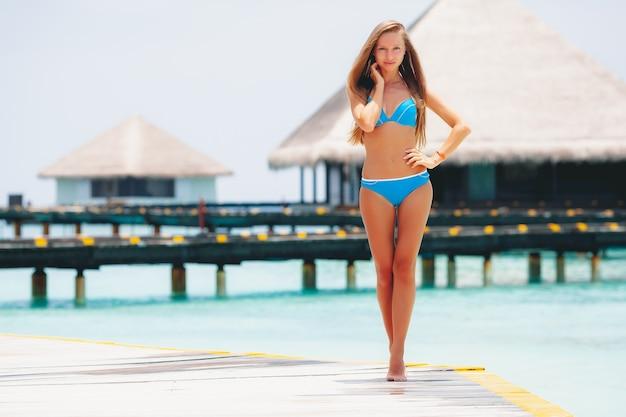 Junges attraktives blondes mädchen im bikini am tropischen strand im resort