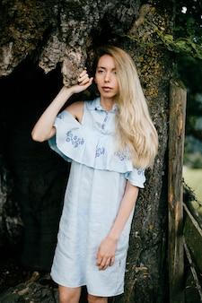 Junges attraktives blondes mädchen im blauen romantischen kleid, das mit altem baum aufwirft
