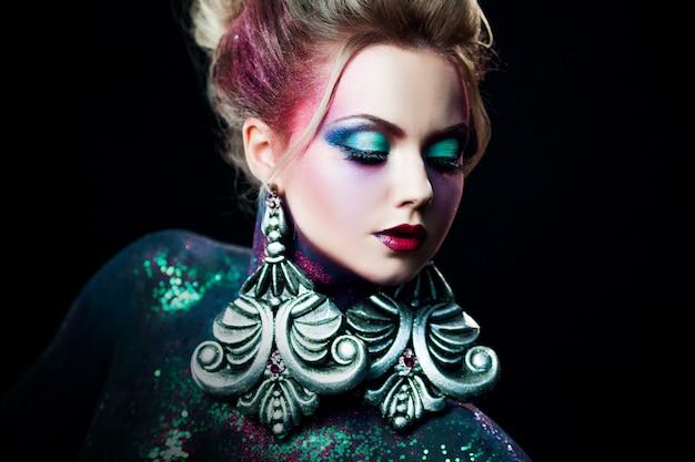 Junges attraktives blondes mädchen im hellen kunst-make-up, hohe haare, körperbemalung. strass und glitzer