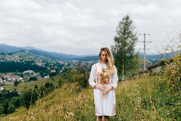 Junges attraktives blondes mädchen im weißen kleid mit verzierung, die mit ährchenstrauß über malerischer landschaftslandschaft aufwirft