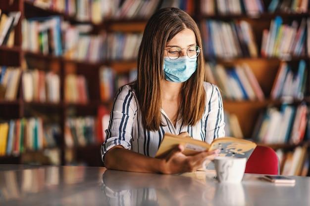 Junges attraktives college-mädchen mit gesichtsmaske, die in bibliothek sitzt und studiert