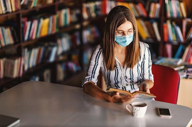Junges attraktives college-mädchen mit gesichtsmaske, die in der bibliothek sitzt und während der koronapandemie studiert.
