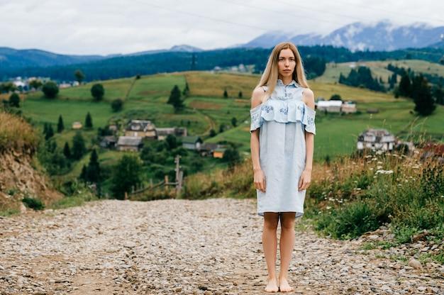 Junges attraktives elegantes blondes mädchen im blauen romantischen kleid, das in der landschaft aufwirft
