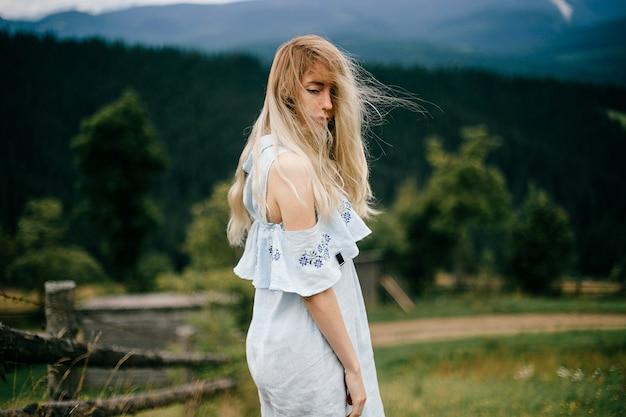 Junges attraktives elegantes blondes mädchen im blauen romantischen kleid, das über malerischer landschaft aufwirft