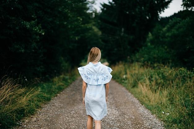 Junges attraktives elegantes blondes mädchen im blauen romantischen kleid, das zurück auf der straße in der landschaft aufwirft