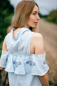 Junges attraktives elegantes blondes mädchen im blauen romantischen kleid, das zurück in der landschaft aufwirft