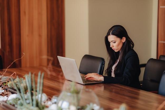 Junges attraktives emotionales mädchen in der geschäftart kleidung, die an einem schreibtisch an einem laptop und an einem telefon sitzt