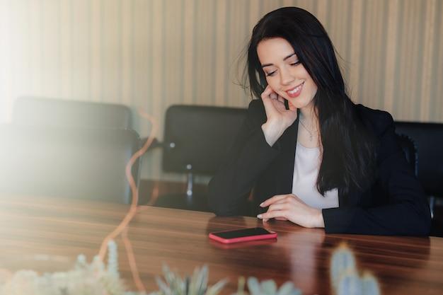 Junges attraktives emotionales mädchen in der geschäftsart kleidet das sitzen am schreibtisch mit telefon
