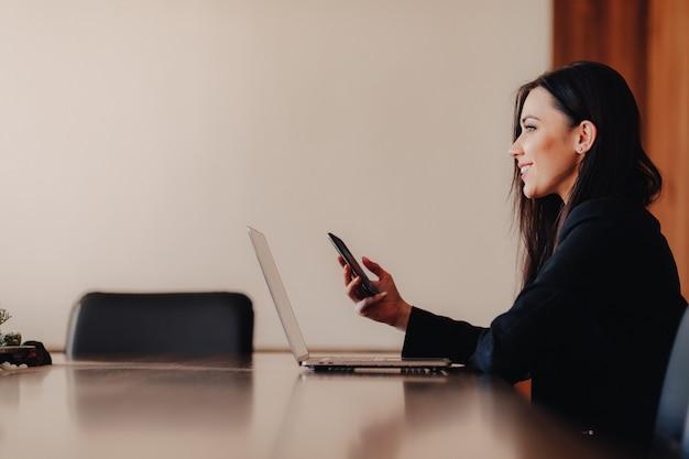 Junges attraktives emotionales mädchen in der geschäftsart kleidung, die an einem schreibtisch an einem laptop und an einem telefon im büro oder im auditorium sitzt