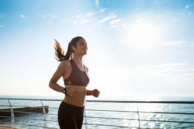 Junges attraktives fitnessmädchen, das mit meer auf hintergrund joggt