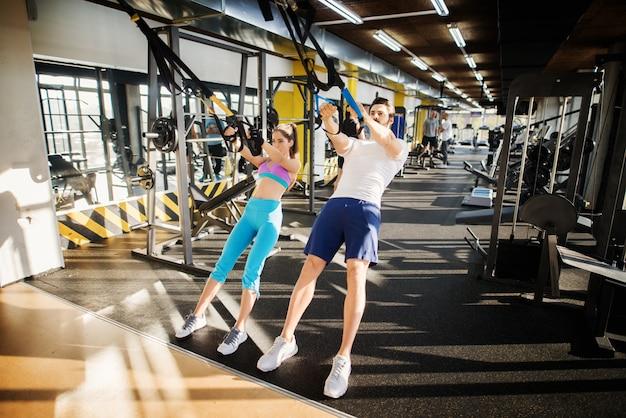 Junges attraktives fitnesspaar, das mit trx im fitnessstudio trainiert.