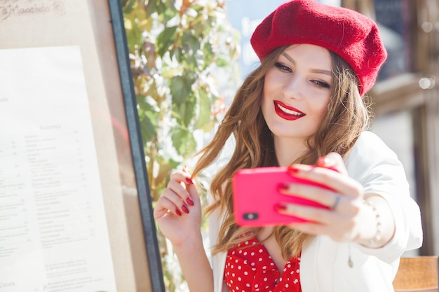 Junges attraktives französisches mädchen, das selfie am handy macht. hübsche dame, die mobile hält.