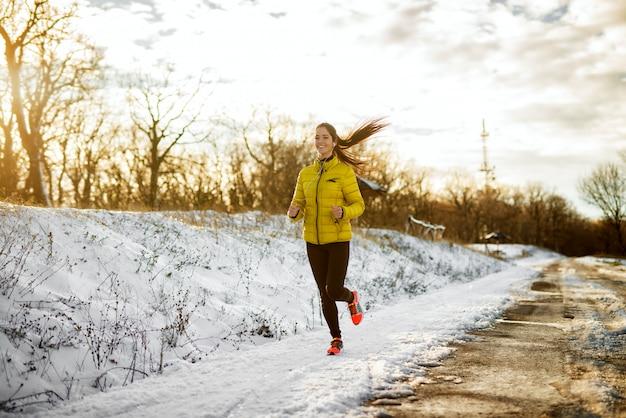 Junges attraktives gesundes läufermädchen, das in wintersportbekleidung auf verschneiter winterstraße draußen mit kopfhörern joggt