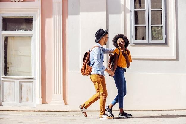 Junges attraktives glückliches gemischtrassiges paar, das draußen an einem schönen sonnigen tag steht, der auf der straße beim gehen flirtet.