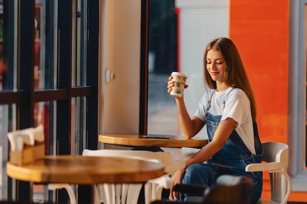 Junges attraktives hübsches mädchen am café mit kaffee und telefon am morgen strahlt