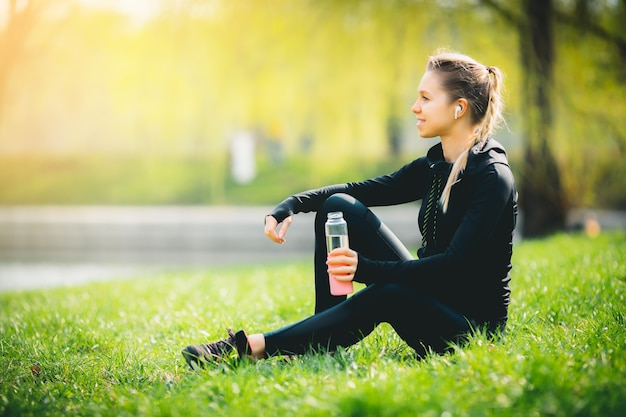 Junges attraktives kaukasisches mädchen im sportanzug, der nach dem laufen im park ruht, auf grastrinkwasser sitzend und lächelnd genießt ihre drahtlosen kopfhörer