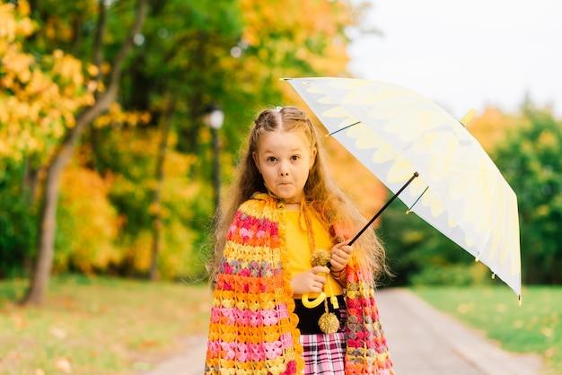 Junges attraktives lächelndes mädchen unter regenschirm im herbstwald