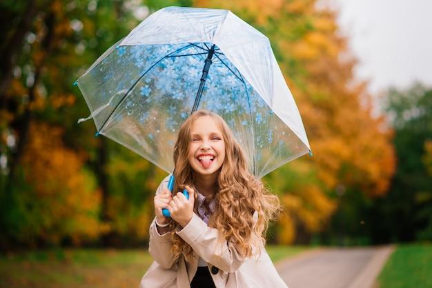 Junges attraktives lächelndes mädchen unter regenschirm in einem herbstwald