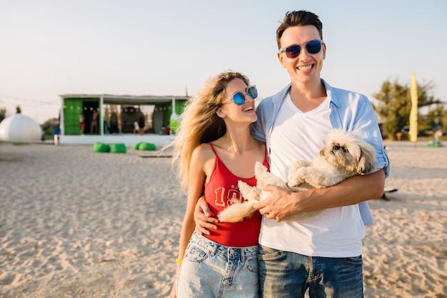 Junges attraktives lächelndes paar, das spaß am strand hat, der mit hund spielt