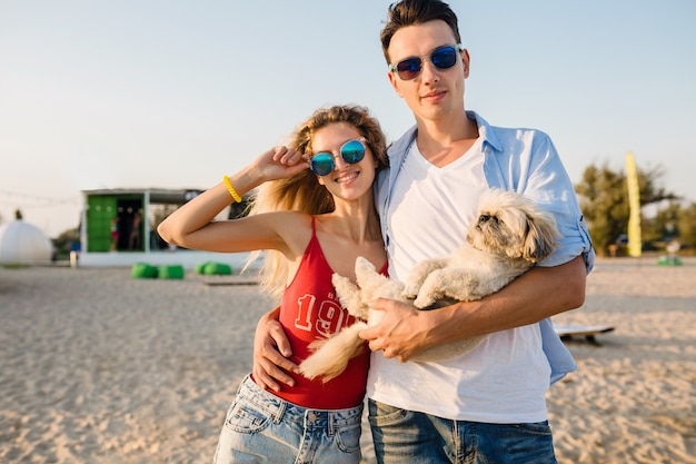Junges attraktives lächelndes paar, das spaß am strand spielt mit hund shih-tsu rasse spielt
