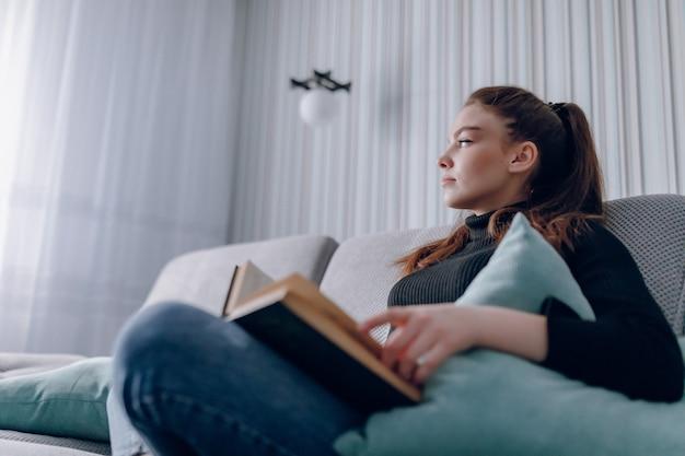 Junges attraktives mädchen auf der couch liest ein papierbuch. geistige entwicklung. nützliche nutzung der zeit zu hause. wohnkomfort.