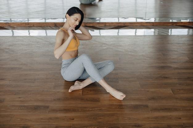 Junges attraktives mädchen auf einem bretterboden, der yoga tut, sich ausdehnt und sich entspannt