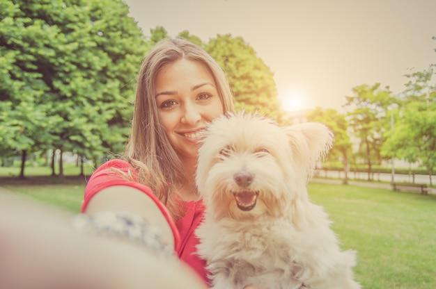 Junges attraktives mädchen, das ein selfie mit ihrem hund nimmt