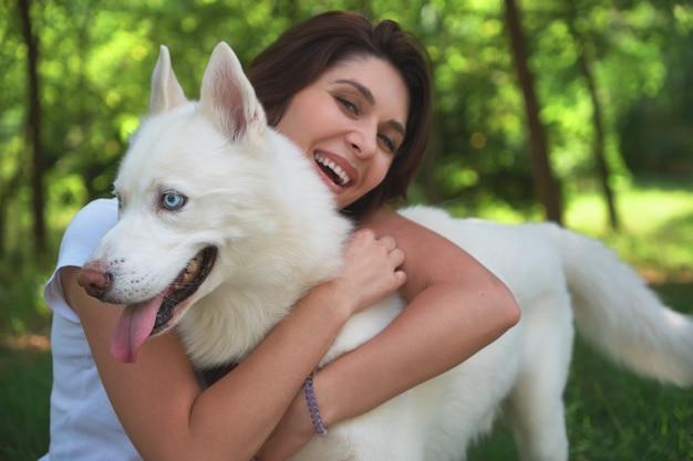 Junges attraktives mädchen, das ihren haustierhund umarmt