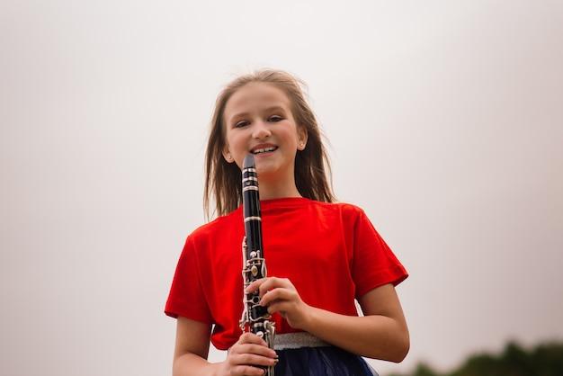 Junges attraktives mädchen, das klarinette, ebenholz im herbstpark spielt