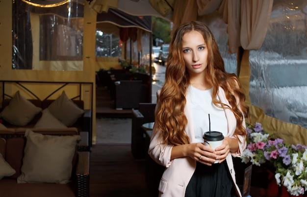 Junges attraktives mädchen hält papiertasse kaffee in ihren händen. regnerischer abend in einem straßencafé.