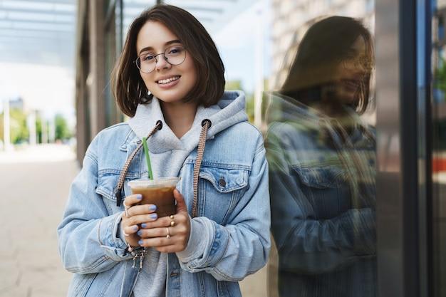 Junges attraktives mädchen in gläsern, jeansjacke, lässig in der stadt spazieren gehen, wochenenden genießen, eislatte trinken, sich auf gebäudewand stützen und kamera mit glücklichem entspanntem ausdruck lächeln.