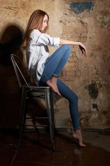 Junges attraktives mädchen oder modell, die ein weißes hemd stationiert auf dem stuhl tragen.