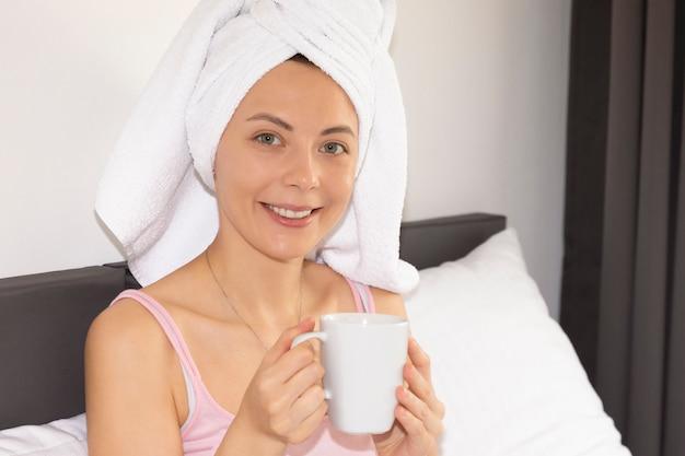 Junges attraktives mädchen sitzt auf dem bett. eine frau genießt das morgendliche erwachen und trinkt ihren morgenkaffee.