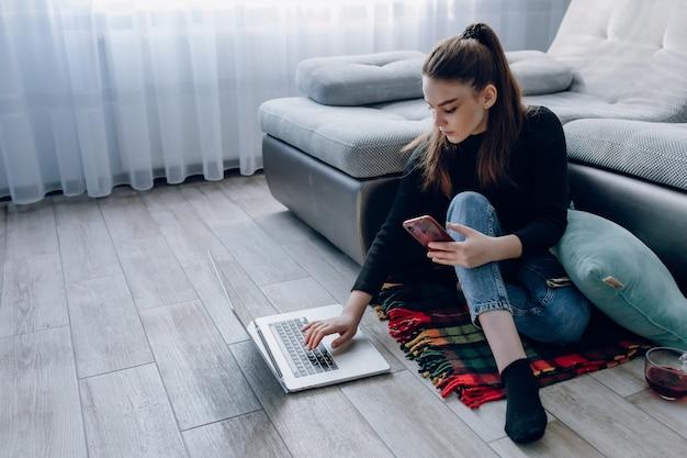 Junges attraktives mädchen zu hause, das mit einem laptop arbeitet und am telefon spricht. komfort und gemütlichkeit zu hause. home office und arbeit von zu hause aus. remote-online-beschäftigung.