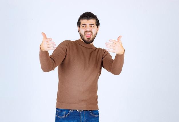 Junges attraktives modell im braunen pullover, der gesten über der weißen wand macht.