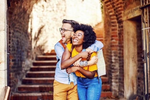 Junges attraktives multikulturelles hipster-paar in liebesumarmung und in einem alten teil der stadt. mann, der eine karte hält. tourismuskonzept.