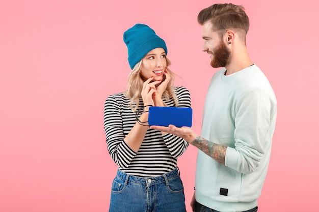 Junges attraktives paar, das musik auf drahtlosem lautsprecher hört, der kühles stilvolles outfit trägt, das glückliche positive stimmung lächelt, die auf isoliertem überraschungsgeschenk der rosa wand aufwirft