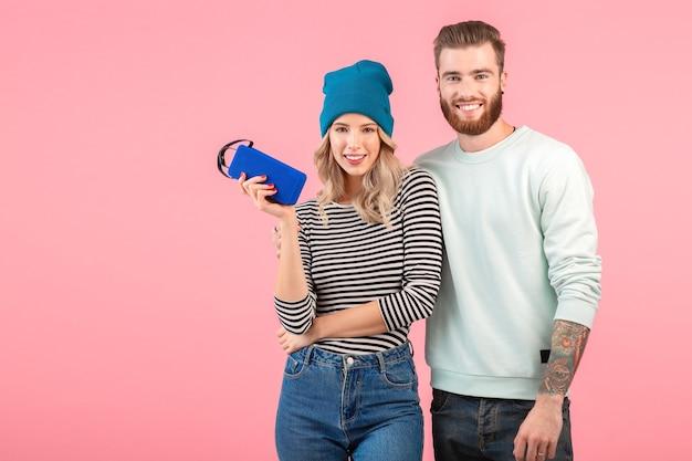 Junges attraktives paar, das musik auf drahtlosem lautsprecher hört und ein cooles, stilvolles outfit trägt, das glückliche positive stimmung posiert auf rosa hintergrund