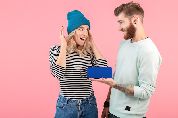 Junges attraktives paar, das musik über drahtlosen lautsprecher hört und ein cooles, stylisches outfit trägt