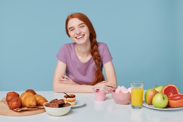 Junges attraktives rothaariges mädchen lächelt verträumt in die obere rechte ecke und sitzt an einem weißen tisch