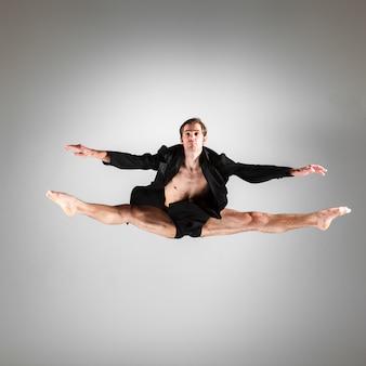 Junges attraktives springen des modernen balletttänzers
