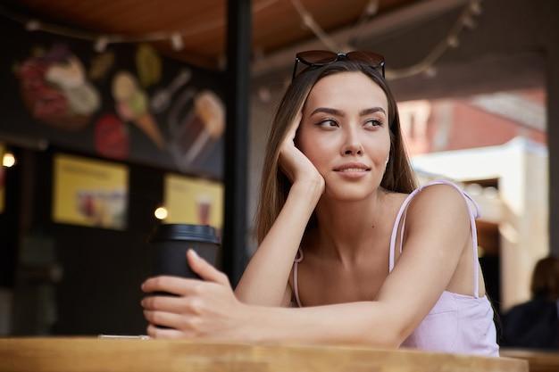 Junges attraktives, stilvolles asiatisches hübsches mädchen, das mit einer tasse kaffee im restaurant sitzt
