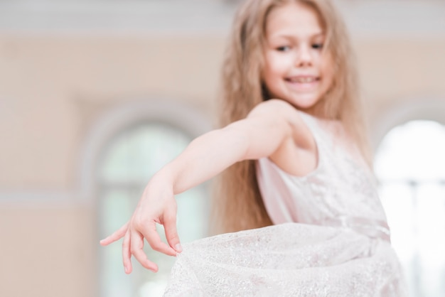 Junges ballerinamädchen mit dem langen blonden haar, das ihr eleganzkleid hält