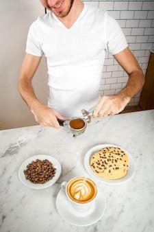 Junges barista, das in einer kaffeestube arbeitet