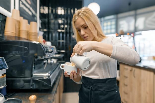 Junges barista, das milch für hält, bereiten tasse kaffee zu