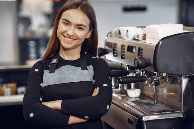 Junges barista-mädchen macht kaffee und lächelt