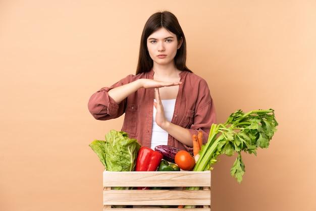 Junges bauernmädchen mit frisch gepflücktem gemüse in einer box, die auszeitgeste macht