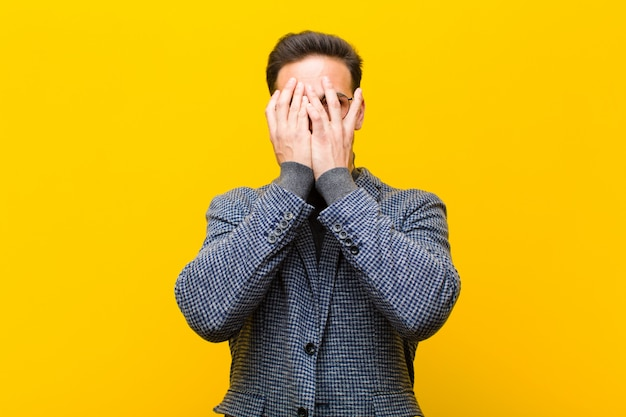 Junges bedeckungsgesicht des gutaussehenden mannes mit den händen, spähend zwischen finger mit überraschtem ausdruck und schauen zur orange seitenwand